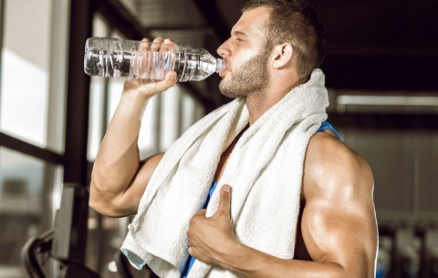 Man drinking water during exercising